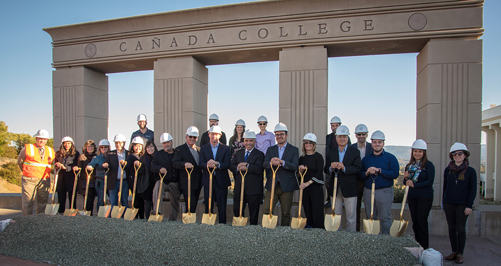 A crowd of people stand with golden shovels and hard hats at the groundbreaking ceremony for the Kinesiology, Wellness, and Aquatics Center at Cañada College