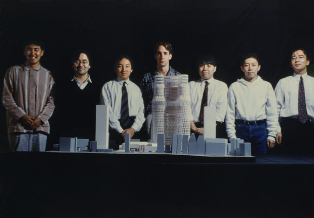 A group of people standing behind an architectural model